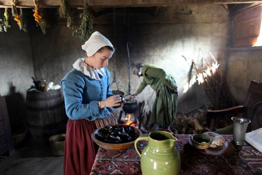 Lucretia Brewster re-enactor and her father-in-law, William, prepare mussels and other food for a 17th-century-style meal. (Photos by Pat Greenhouse/Globe Staff)