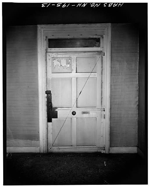 Main entrance door looking south. Note wide size with transom light and hand-wrought heart-shaped hinges